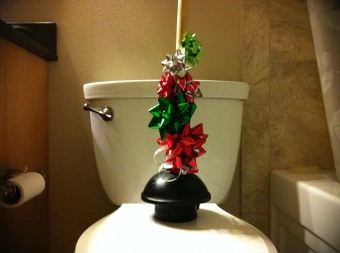 Plunger with Christmas bows on a toilet